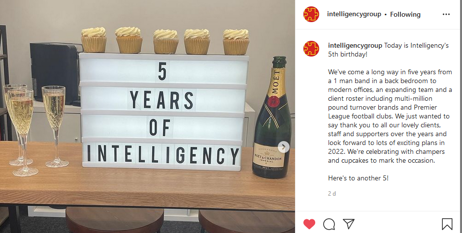 """An Instagram screenshot depicting 3 glasses of champagne to the right of a lightbox which reads """"5 YEARS OF INTELLIGENCY"""" and to the right is an opened bottle of Champagne."""